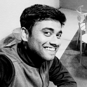 A black and white profile photo of Mathew John - he is smiling and looking at the camera