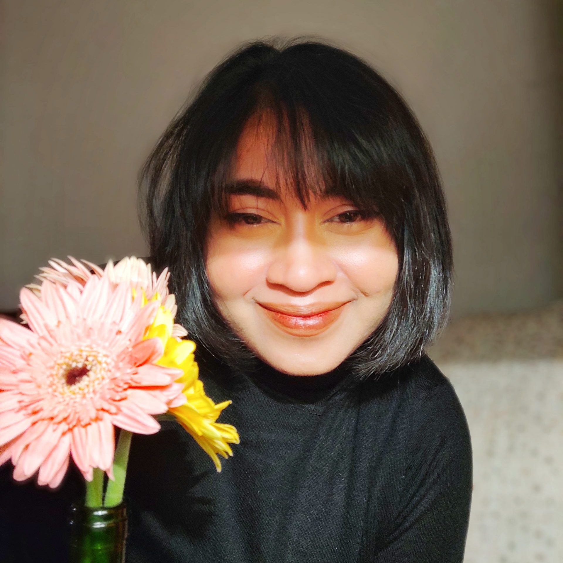 Photo of Moumita Das in a black top looking at the camera and smiling. She is indoors next to a bouquet of large flowers