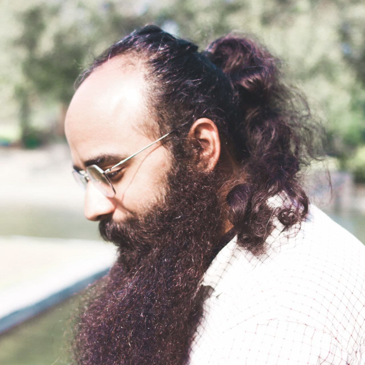 Photo of Guneet Narula's side profile - he is wearing a white shirt and spectacles and is looking down. His long hair and beard are visible with some greenery in the background.